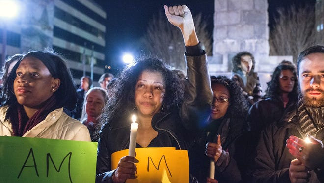 Pamela Washington raises her arm in solidarity during a peaceful protest at Pack Square in Asheville, N.C., on Nov. 25, the day after a grand jury declined to indict a police officer in the shooting death of Michael Brown, an unarmed black teenager.