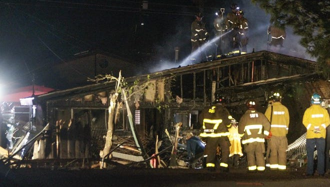 Firefighters hose down the roof of a house that was damaged by fire after a small plane crashed into it in San Diego, Saturday, Dec. 9, 2017. Authorities in southern California say at least two people are dead after a small plane crashed into the home. The single-engine, six-seat Beech BE36 Bonanza had taken off from Montgomery Field about a half mile away.