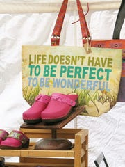 Totes with meaning and hand-made clogs are popular accessories at Tessa Clogs' booth Vail Market and Art Show.