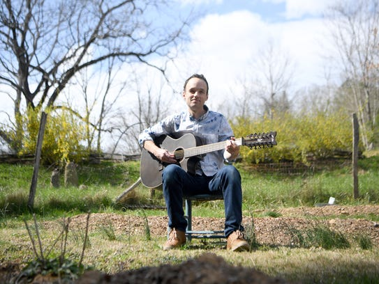 Drew Heller, a member of Toubab Krewe, poses in a garden at Seed Programs International in Asheville. The nonprofit will benefit from the band's spring tour, which makes a stop in Asheville on April 20-21 at Ellington Underground.