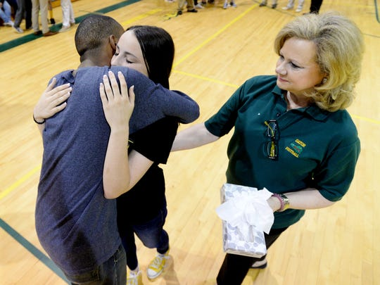 Daughter of Richard Lary, Ally Lary, gets a hug from Justin Brown after she gives him the green rubber bracelet her dad wore all the time Monday morning memorial for Richard Lary.