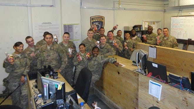 Troops hold up bags of treats that were sent to them by Alpha Sigma Tau Sorority during its 10th annual Treats 4 Troops campaign last year.