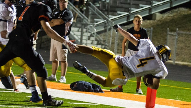 Iowa City Regina's Nick Phillips (4) dives into the endzone for a touchdown at Spartan Stadium in Solon on Friday September 6, 2013. The rivalry was won by Regina in a 38-0 blowout win over the Spartans.