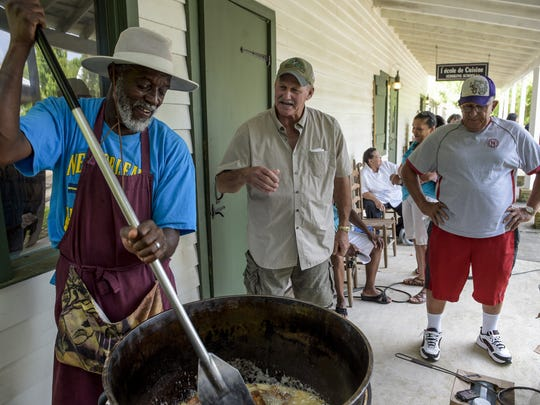 Edmond Alexander Jr. demonstrates cracklin cooking during Creole Culture Day at Vermilionville.
