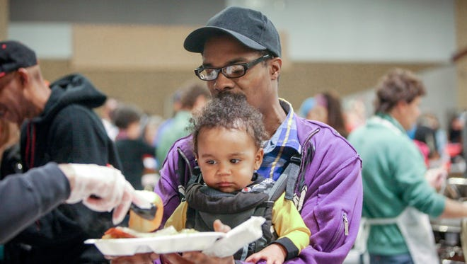 Johnny Ballard and his son Johnny Noble Ballard wait in line to receive their food during the 28th annual Mental Health America of Northern Kentucky and Southwest Ohio Christmas dinner.