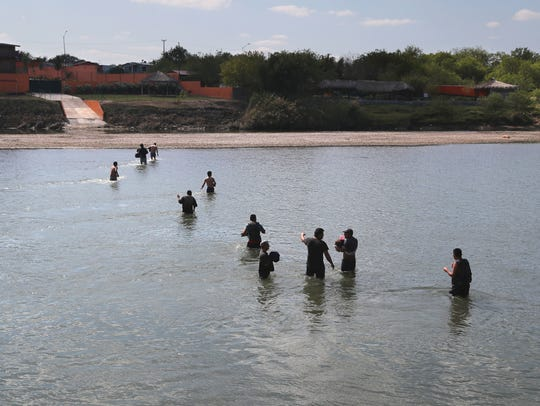 Would-be immigrants wade across the Rio Grande at the