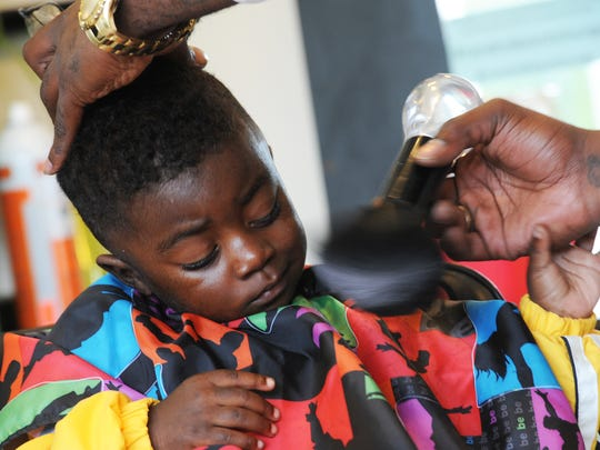 Bryant Walker finishes a haircut for 2-year-old Mason Washington on Tuesday, Oct. 27, 2015. Walker and fellow hairstylist Courtney Johnson are coordinating a hair cuts for toys drive which will be held at the Accomac Elks Lodge on Dec. 6.