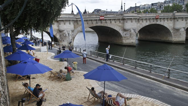 Tourists and Parisians take advantage of Paris-Plages, an artificial beach set up on the right bank of the Seine River, with palm trees, outdoor showers and hammocks.