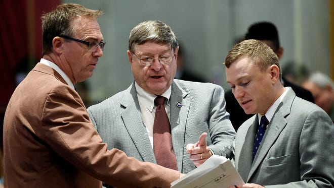 In this file photo, former Rep. Rick Womick, R-Rockvale, left, and Rep. Harry Brooks, R-Knoxville speak with a legislative aide during the final days of the session on Tuesday April 19, 2016, in Nashville, TN