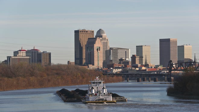 A barge moves up the Ohio River after clearing the McAlpine Locks and Dam in Louisville's Portland neighborhood as the city's skyline looms in the background. The Falls of the Ohio are the only falls in the entire length of the 981 miles of the Ohio River. The widest point of the Ohio is one mile across, just north of Louisville.