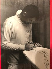 Photo of Pat O'Hare working on a board he made. Photo