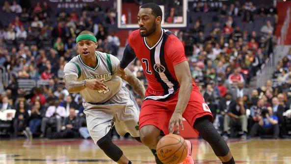 John Wall (2) drives to the basket past Boston Celtics