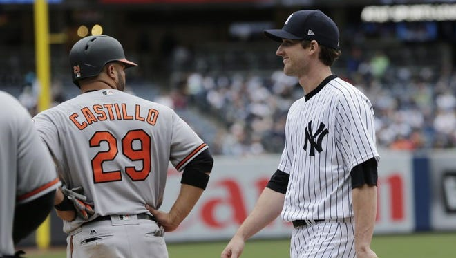 New York Yankees relief pitcher Bryan Mitchell talks with the Baltimore Orioles' Welington Castillo while playing first base.