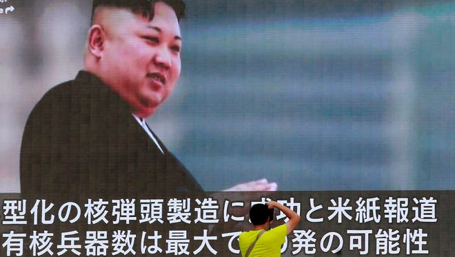 Man takes a photo of a TV news program showing North Korean leader Kim Jong Un, Tokyo, Aug. 9, 2017.