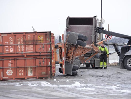 Three heavy wreckers work on overturned tractor-trailer