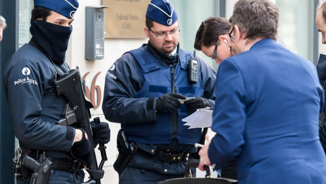 Police checks the identity of people who want to enter a government building in Brussels, Friday, Jan. 16, 2015. Thirteen people were detained in Belgium and two arrested in France in an anti-terror sweep following a firefight in which two suspected terrorists were killed in the eastern city of Verviers on Thursday.