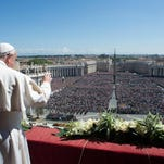 Pope Francis waves to the crowd from the balcony of St. Peter's Basilica where he delivered the Urbi et Orbi (Latin for to the city and to the world) at the end of the Easter Mass in St. Peter's Square at the the Vatican Sunday.