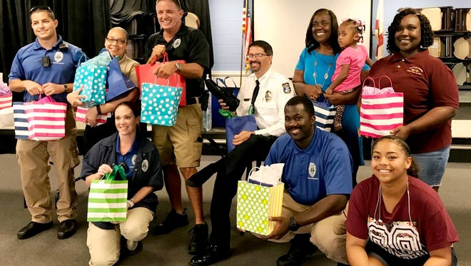 Stuart Police Chief David Dyess (seated, in white shirt), East Stuart Partnership president Thelma Washington (standing in blue dress), members of the Stuart Police Department and staff of the Gertrude Walden Child Care Center and East 10th Street Recreation Center distribute 120 pairs of sneakers to children in the program.