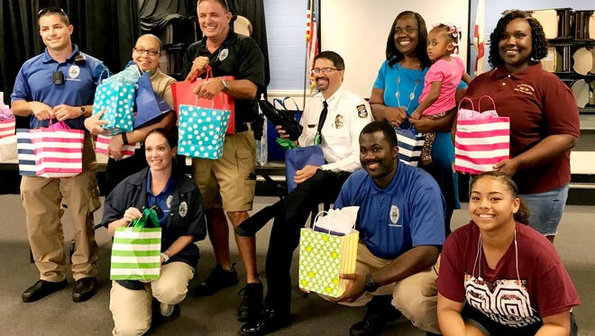 Chief David Dyess, seated, in white shirt, East Stuart Partnership President Thelma Washington, standing in blue dress, members of the Stuart PoliceDepartment and staff of the Gertrude Walden Child Care Center and East 10th Street Recreation Center prepare to distribute 120 pairs of sneakers to children in the program.