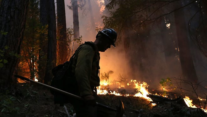 GROVELAND, CA - AUGUST 22:  A firefighter from the Colorado based Long Canyon Fire Department monitors a back fire while battling the Rim Fire on August 22, 2013 in Groveland, California. The Rim Fire continues to burn out of control and threatens 2,500 homes outside of Yosemite National Park. Over 1,000 firefighters are battling the blaze that was reduced to only 2 percent containment after it nearly tripled in size overnight.  (Photo by Justin Sullivan/Getty Images) ORG XMIT: 177614237 ORIG FILE ID: 177315228