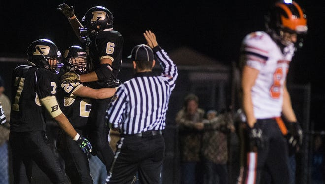 """Biglerville High School is scheduled to play sports on a """"conditional"""" basis this fall. In this photo from 2015, Dayne Showers is congratulated by teammates after scoring a touchdown during the first half of a win over Hanover."""