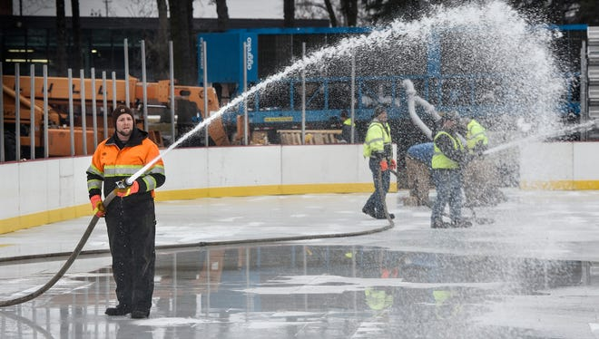 Crews spray water to form the ice surface on the Hockey Day Minnesota rink Wednesday, Jan. 10, at Eastman Park in St. Cloud. The rink features an under-ice freezing system, boards, glass and lighting. Crews were also installing bleachers around the rink Wednesday afternoon.