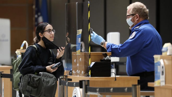 In this photo taken May 18, 2020, a traveler pulls down her mask so that a TSA officer can verify her identity at a security check point at Seattle Tacoma International Airport, in SeaTac, Wash.