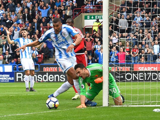 Huddersfield Town's Collin Quaner, center, has an attempt on goal stopped by Watford's goalkeeper Orestis Karnezis during their English Premier League soccer match at the John Smith's Stadium, Huddersfield, England, Saturday, April 14, 2018. (Dave Howarth/PA via AP)