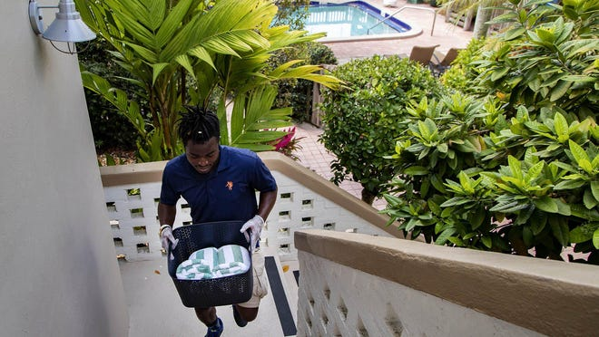 Benson Bois, employee at Crane's Beach House, delivers pool towels to a guest room in Delray Beach, Thursday, March 26, 2020. The boutique hotel is providing guests reduced prices for extended stays.