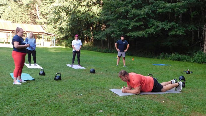 Justin Hoffman, co-owner of Movement, Strength and Fitness in Ilion, demonstrates a warm-up exercise Thursday during a class at Russell Park.
