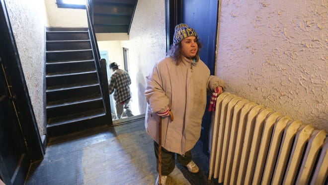 Caroline Etheridge keeps her coat on inside the Glendower Apartments, where the radiators no longer put out any heat.