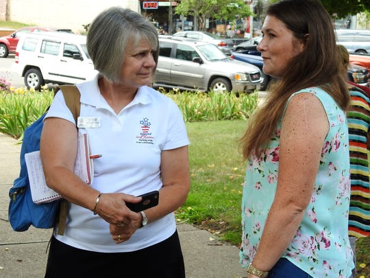 America in Bloom judge Susie Stratton talks with Jandi Adams, Executive Director of Clary Gardens, outside of the Coshocton County Courthouse.