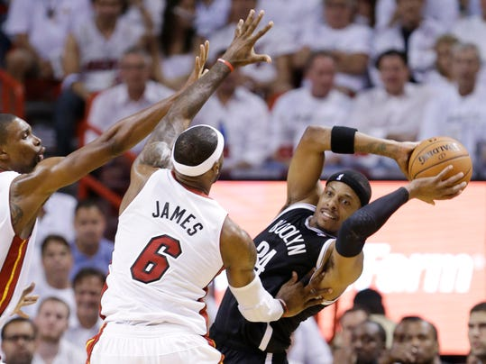 Brooklyn Nets forward Paul Pierce (34) looks for an open teammate past Miami Heat forward LeBron James (6) and center Chris Bosh, left, during the first half of Game 2 of an Eastern Conference semifinal basketball game, Thursday, May 8, 2014 in Miami. (AP Photo/Wilfredo Lee)