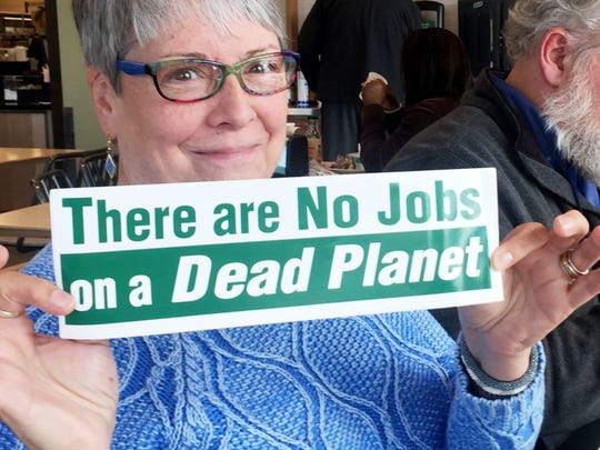 Ellen Newton-Stetson holds an environmental bumper sticker that shows her opinion of the estimated 1,500 construction jobs the Bayou Bridge Pipeline will bring to the state.