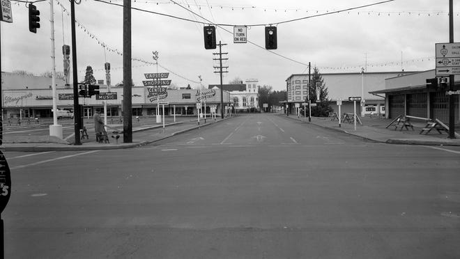 Capitol Shopping Center is seen in January 1958 from Marion and 12th streets NE. Margwen's, Flowers by Jary, Wiltsey-Weathers Music and Shyrock's Mens Wear are seen on the left side of the photo while Sears is on the right side.