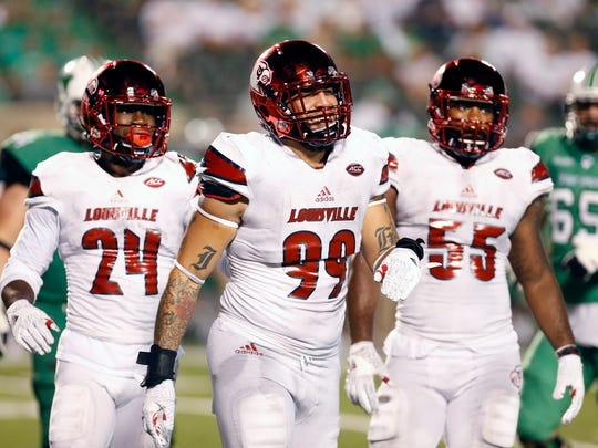 Louisville's James Hearns (99) is all smiles after he and teammates Zykiesis Cannon (24) and Keith Kelsey stuff a run by Marshall. Sept. 24, 2016