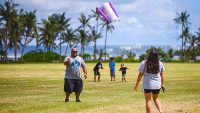 In this Nov. 10, 2017, file photo, parents Tristan, left, and Jaime Fejeran, launch the second of two kites as they and their five children enjoy some quality family time together at the War in the Pacific National Historical Park - Asan Beach Unit.
