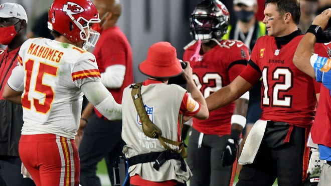 In this Nov. 29, 2020, file photo, Tampa Bay Buccaneers quarterback Tom Brady (12) congratulates Kansas City Chiefs quarterback Patrick Mahomes (15) after their NFL football game in Tampa, Fla. The Super Bowl matchup features the most accomplished quarterback ever to play the game who is still thriving at age 43 in Brady against the young gun who is rewriting record books at age 25. (AP Photo/Jason Behnken, File)