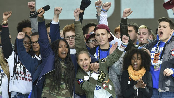 "Marjory Stoneman Douglas High School student Emma Gonzalez gathers with other students on stage during the March for Our Lives Rally in Washington, on March 24, 2018.  Student organizers of gun control rallies that drew hundreds of thousands to US streets vowed on March 25, 2018 there will be no letup in their campaign for reform. The nationwide protests on Saturday were by far the largest in nearly two decades, part of a reignited gun control debate sparked by last month's killings at a Florida high school.""This is not the end. This is just the beginning,"" Emma Gonzalez, a leader of the movement, said on CBS's ""Face the Nation.""  / AFP PHOTO / Nicholas KammNICHOLAS KAMM/AFP/Getty Images ORIG FILE ID: AFP_1364QY"