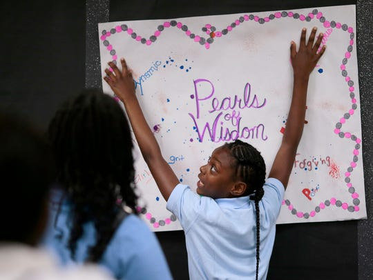 Tamia Leonard hangs a poster that she designed with