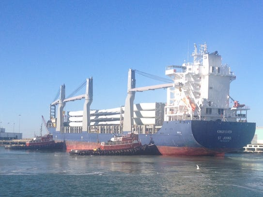 A tug moves a cargo vessel carrying windmill blades