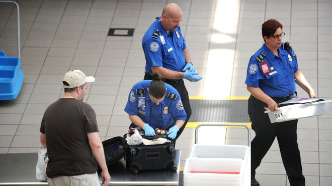 A Transportation Security Administration  agent checks the luggage of a passenger in 2011 at Orlando International Airport.