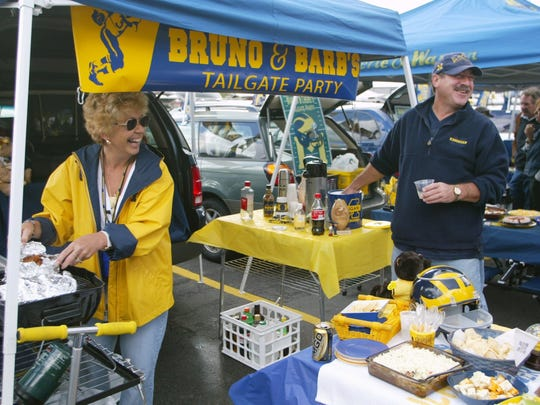 Barbara Jandasek, left, and husband Bruno Jandasek smile and welcome friends to their tailgate party in the parking lot next to Michigan Stadium in 2003.