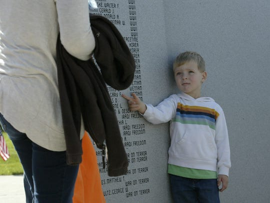 Grant Karls points to the name of his grandfather after the rededication ceremony for the Sheboygan County Veterans Memorial on Saturday, October 10 in Sheboygan