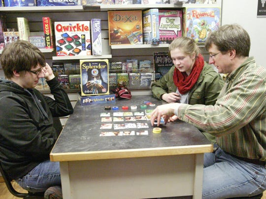Erik Potyen, left, plays a game with his sister, Rachel, and father, Mark, during a game night at The GameBoard in Sheboygan.