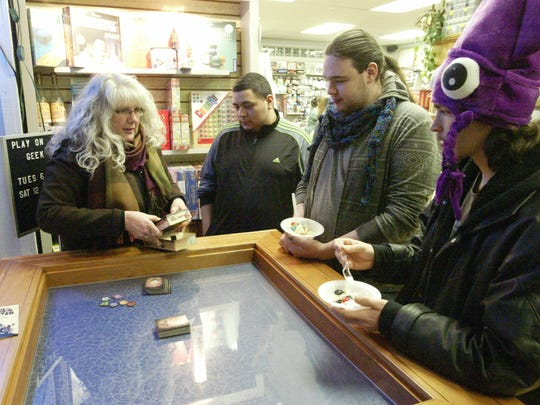 The GameBoard owner Lynn Potyen teaches Jorge Hernandez, Jared Duebner, and James Learman how to play a new game, Three Cheers for Master, at a special game night at the store in partnership with the YouTube channel Geek and Sundry.