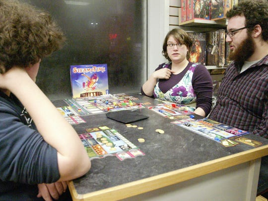 Husband and wife Alonzoeh Stone, right, and Alix Walters play the game Steam Time against Trenton Hall and Alex Potyen (not pictured) during a special game night at The GameBoard.