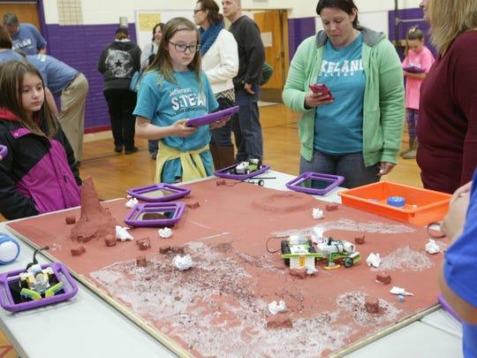 Kadence Paul, center, operates a lego creation on a mock Mars terrain using an iPad.