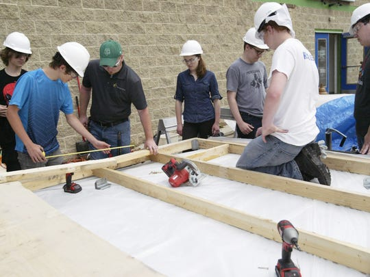 IDEAS Academy teacher Tim Pasche, center, instructs his engineering class as they work on a portable shelter that will be donated to a homeless veteran.