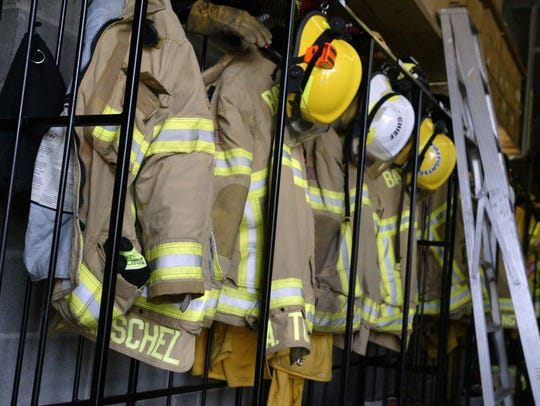 Firefighter jackets and helmets hang on hooks inside